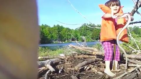 Félelemetes, ahogyan ez kislány dobálja a hatalmas kígyót