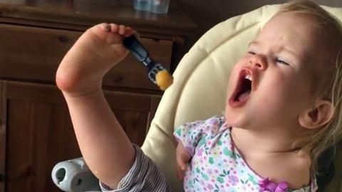 Lábbal eszik az asztalnál a kar nélküli kislány – videó