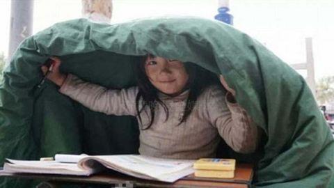 Szívfacsaró fotó: így írja a leckét a hajléktalan kislány