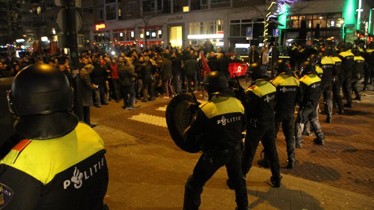 A holland rohamrendőrök farkasszemet néznek a török tüntetőkkel Rotterdamban, március 12-én.