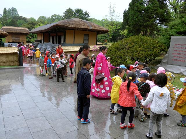 A gyerekeket esőben is terelik Kim Ir Szen szülőházához