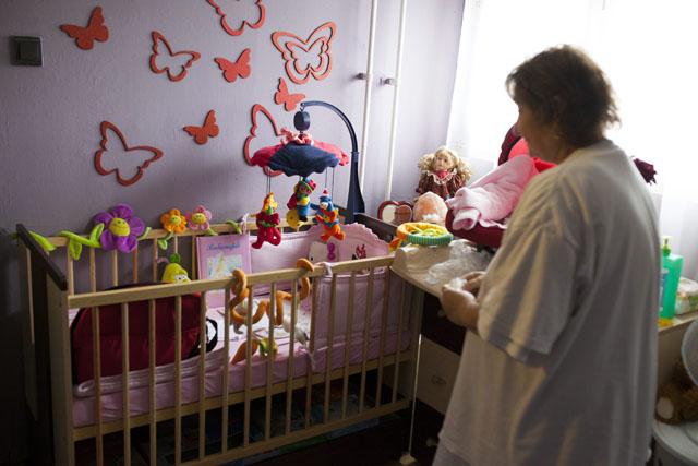 Markusovszky Kórház Szülészeti Osztályáról ellopott, előkerült újszülött csecsemő dédnagymamája áll a gyermek ágya előtt az otthonában (Fotó: MTI)