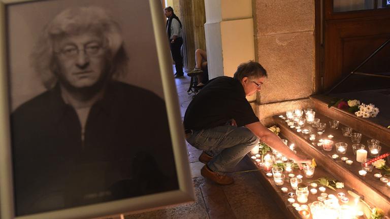 Egy megemlékező mécsest gyújt az előző napon elhunyt Esterházy Péter író emlékére rendezett felolvasóesten a Petőfi Irodalmi Múzeumban 2016. július 15-én. MTI Fotó: Kovács Tamás
