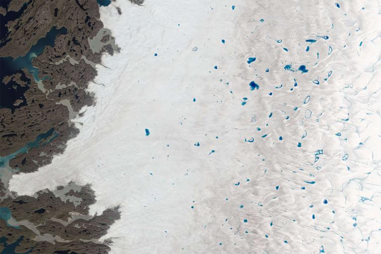 A kék pöttyök a műholdképen az olvadás miatt megjelenő tavak (Fotó: NASA)