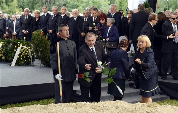 Lezsák Sándor rózsát dob Csoóri Sándor sírjába - Fotó: MTI - Illyés Tibor