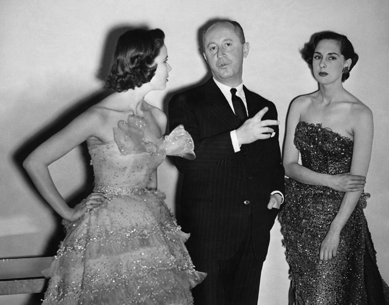 Dior két modellel beszélget egy londoni divatbemutatón 1955-ben (Fotó: Hulton Deutsch/Corbis)
