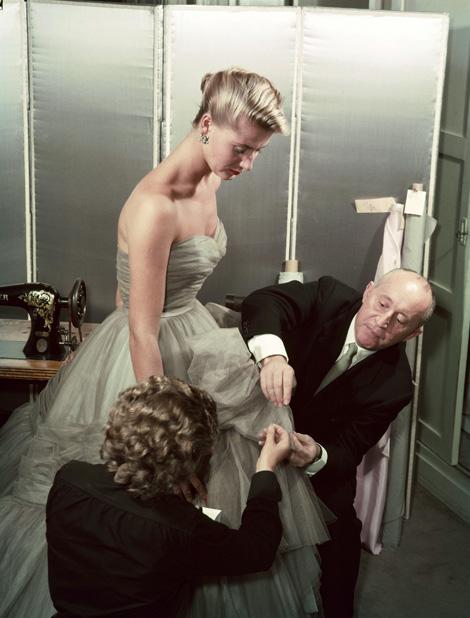 Christian Dior megigazítja a ruhát egy modellen (Fotó: Getty Images)