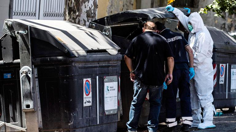 Emberi testrészeket tartalmazó kukát vizsgálnak rendőrök Rómában 2017. augusztus 16-án.