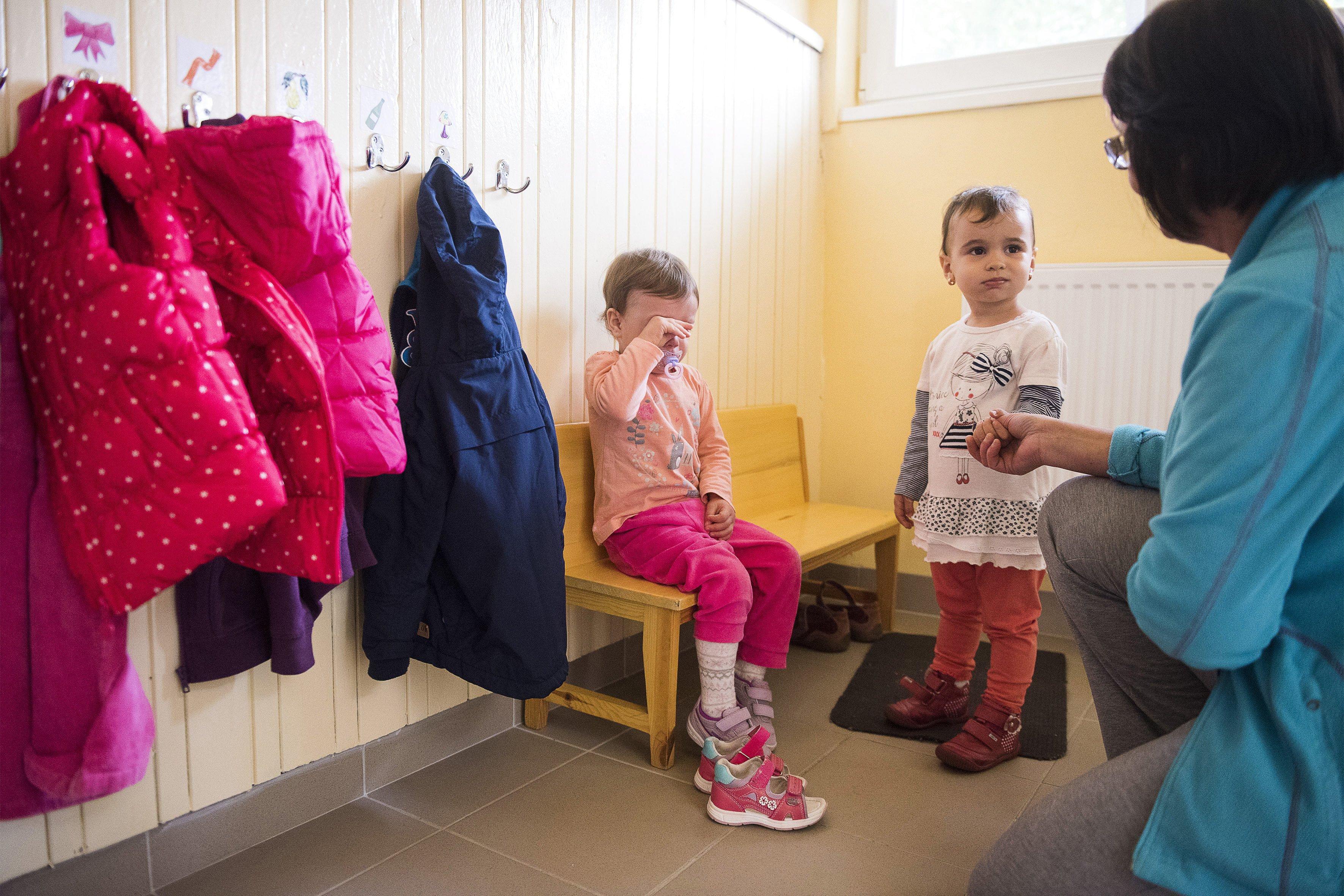Gondozónő nyugtatgat egy negyedik napja bölcsődés kislányt (fotó: MTI/Balázs Attila)