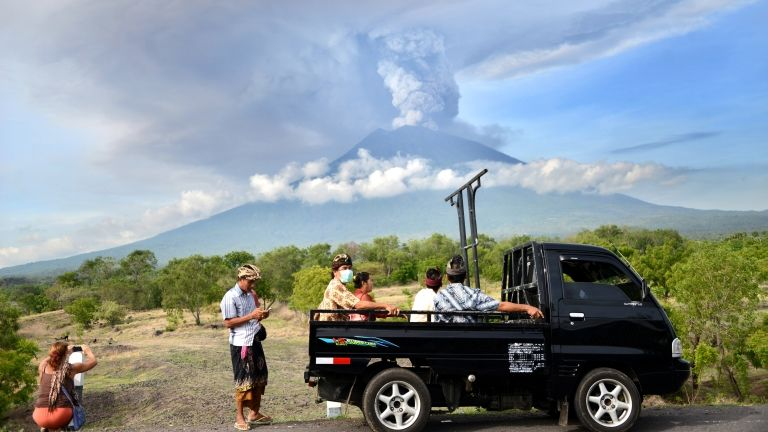 Emberek Balin, a háttérben kitört vulkánnal (fotó: AFP/Sonny Tumbelaka)