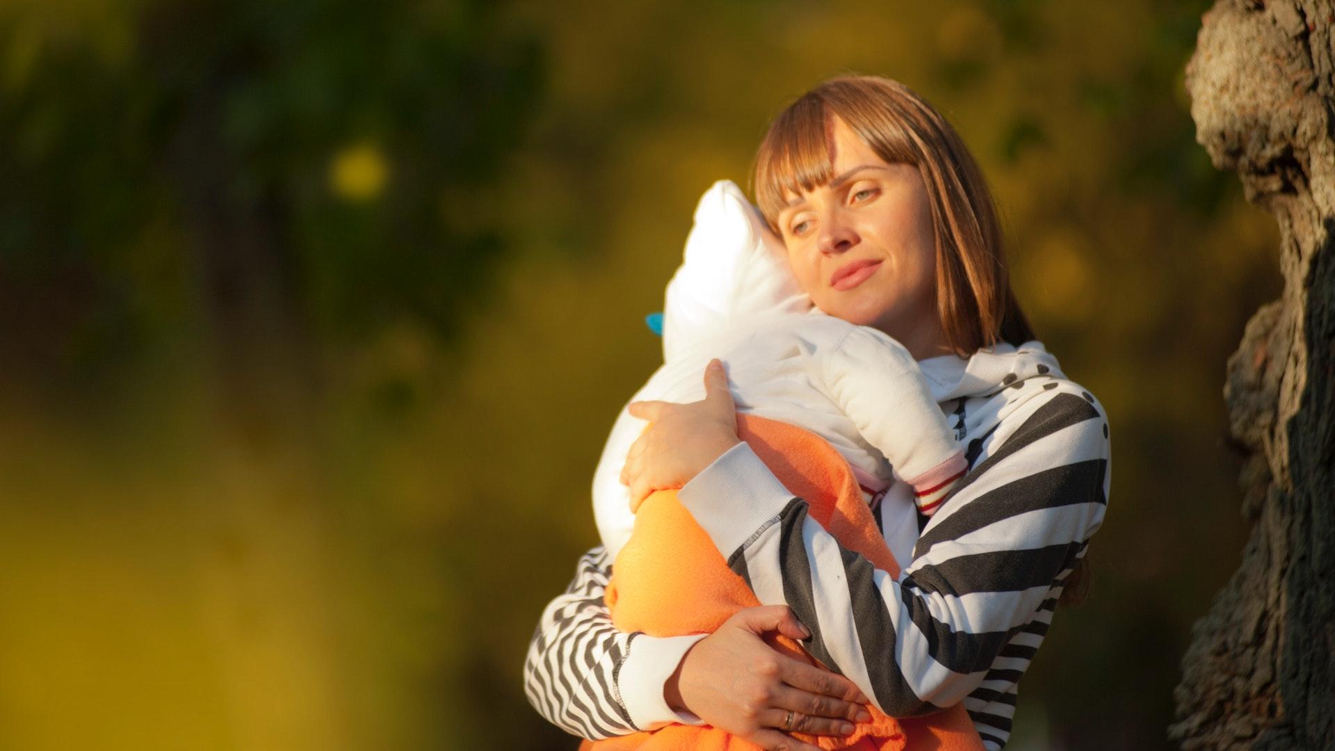 kisbabát tartó nő