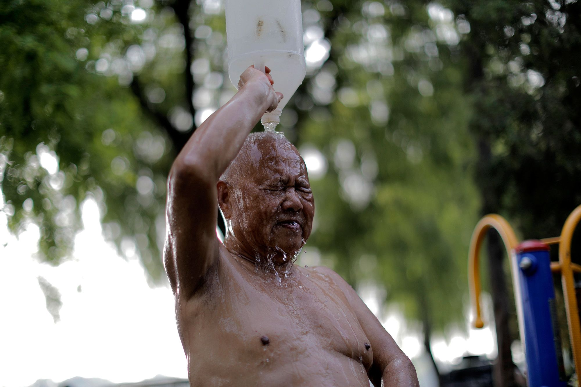 Leöblíti magáról a tóvizet egy fürdőző a pekingi Houhaj tó partján 2019. június 20-án, amikor 35 fokot mértek a kínai fővárosban. Fotó: MTI/EPA/Vu Hong