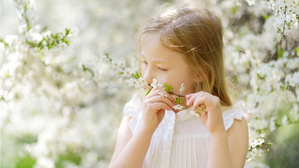 boldog gyermek szagolgatja a növényt