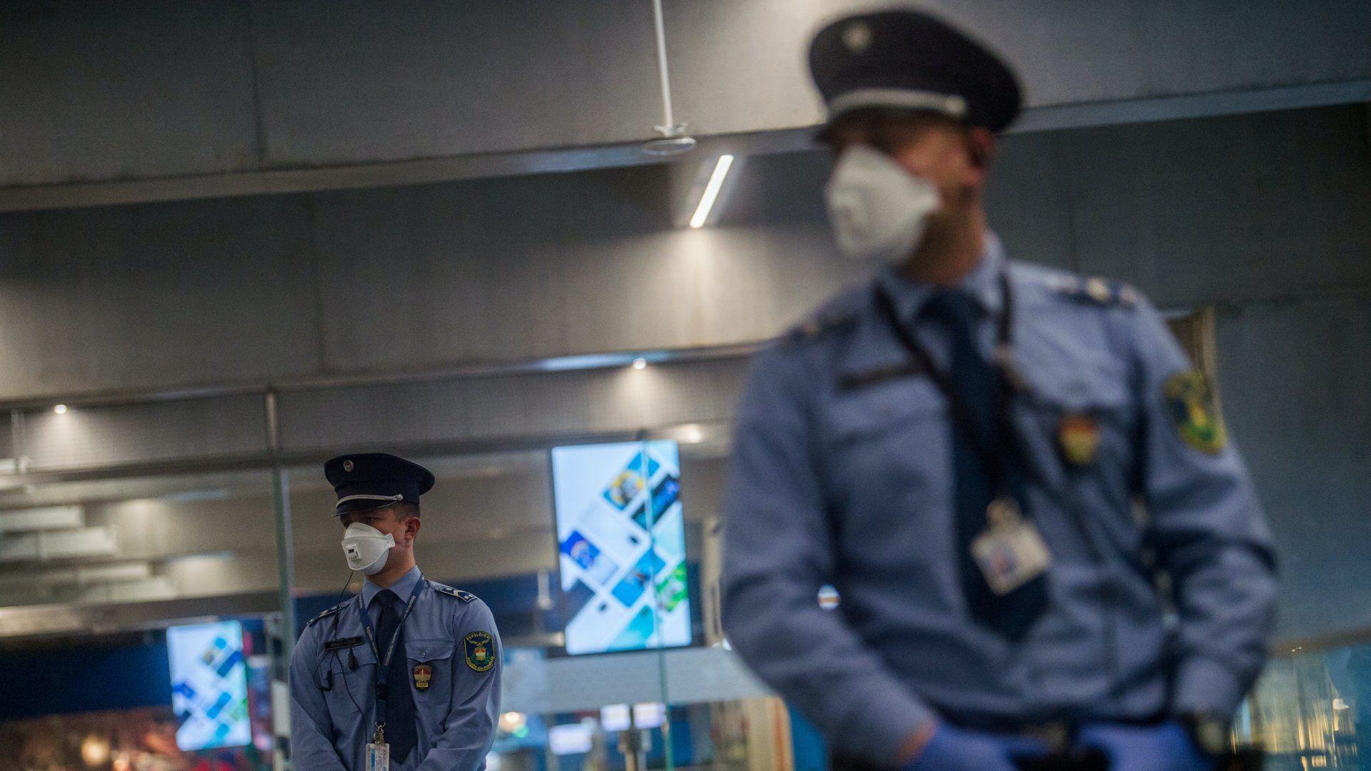 Egészségügyi maszkot viselő rendőrök a Liszt Ferenc-repülőtéren 2020. február 5-én (fotó: MTI/Balogh Zoltán)