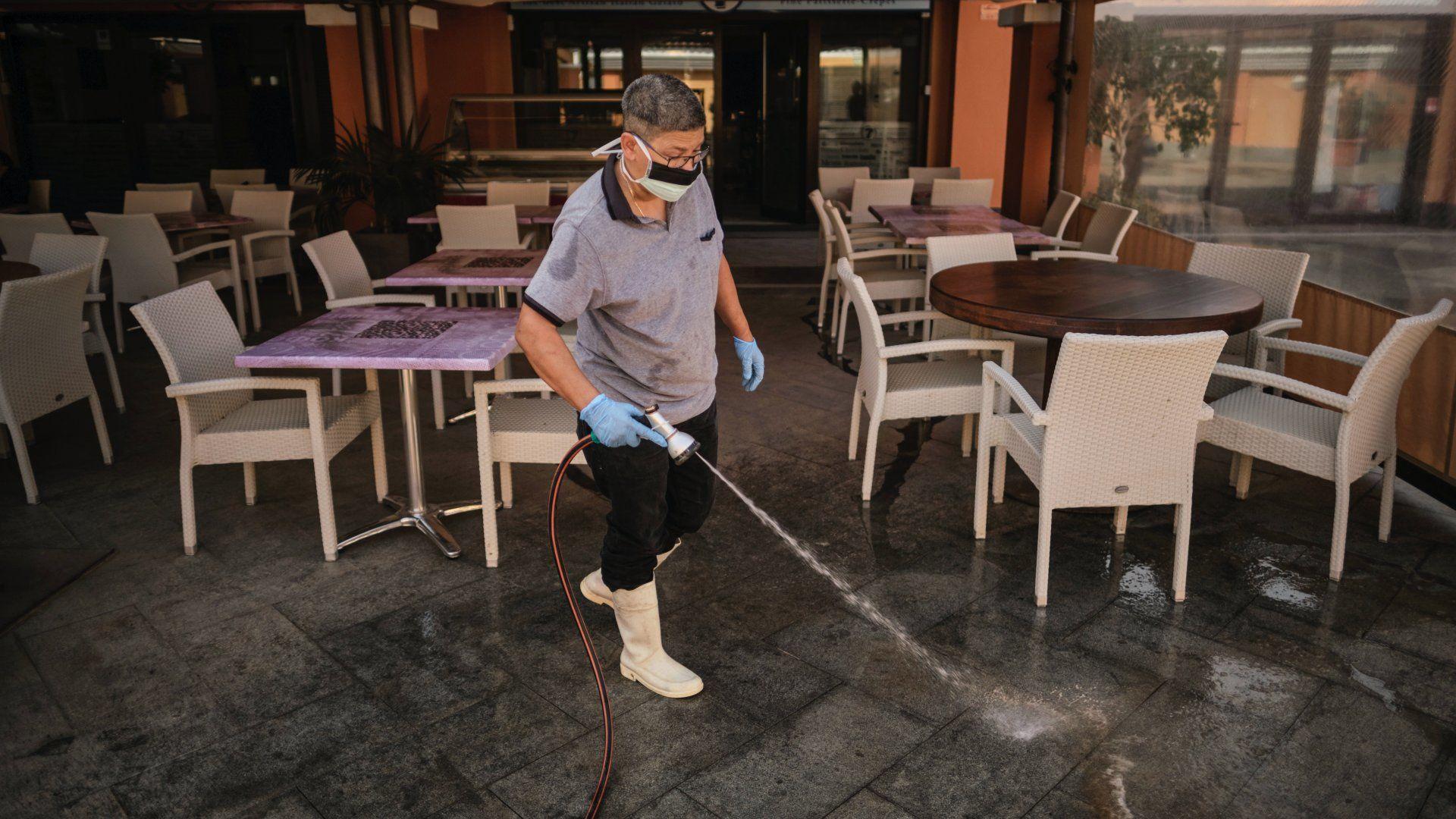 Szájmaszkot viselő férfi fertőtlenítést végez a Tenerife nyugati partjánál lévő Costa Adeje üdülőhely bevásárlóközpontjának teraszán 2020. február 26-án (Fotó: MTI/AP)