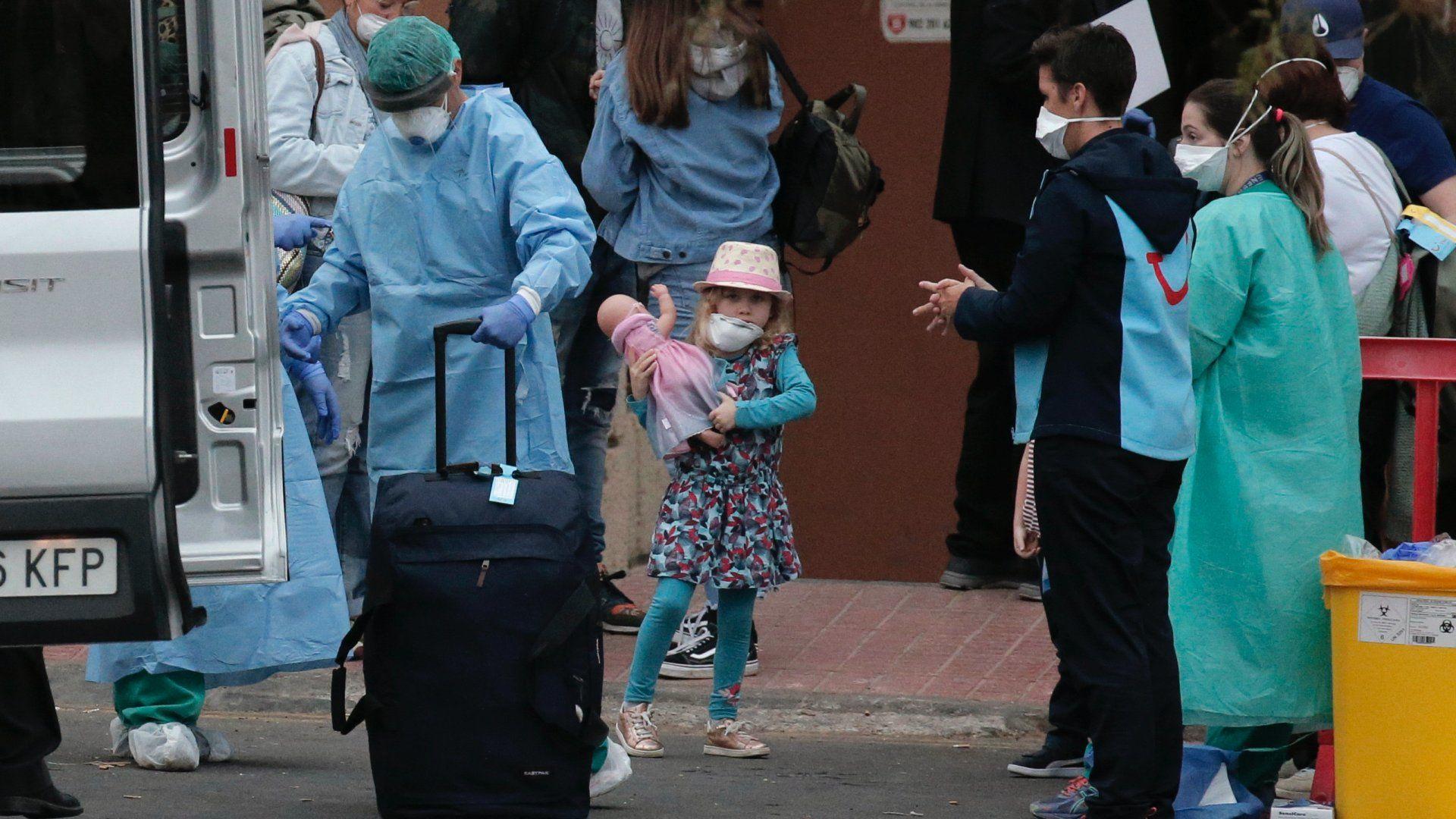 Védőruházatot viselő egészségügyi személyzet segít a távozni készülő vendégeknek a Tenerife nyugati partjánál lévõ La Caleta üdülőhely H10 Costa Adeje Palace nevű szállodájában 2020. február 28-án (Fotó: MTI/AP/Joan Mateu)