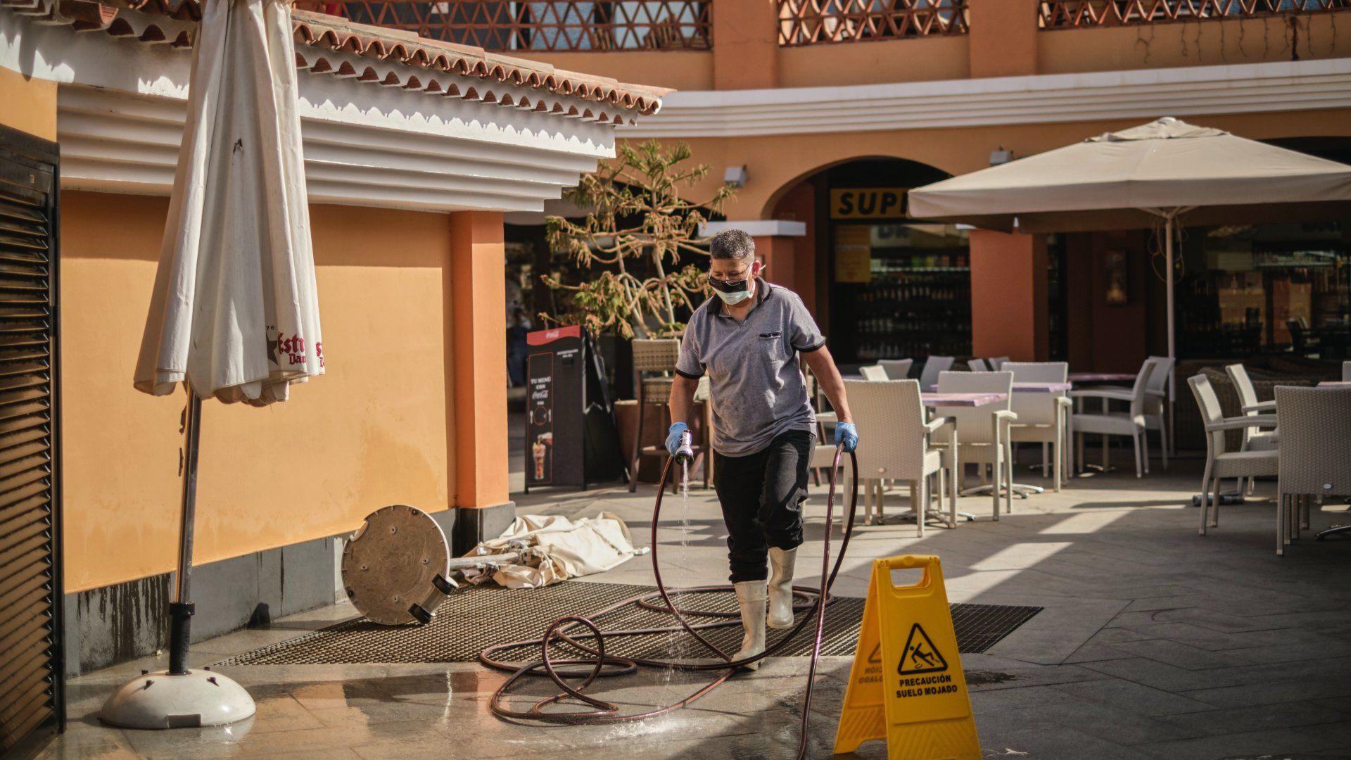 Szájmaszkot viselõ férfi fertőtlenítést végez a Tenerife nyugati partjánál lévő Costa Adeje üdülőhely bevásárlóközpontjának teraszán 2020. február 26-án (Fotó: MTI/AP)