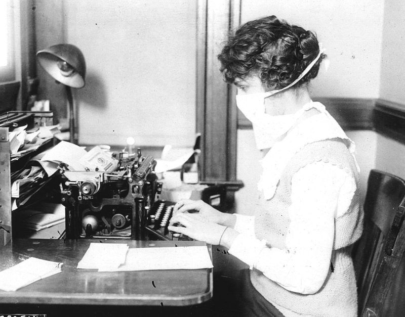 A typist wears mask while working at her office desk, during the influenza epidemic, 1918. (Photo by PhotoQuest/Getty Images)