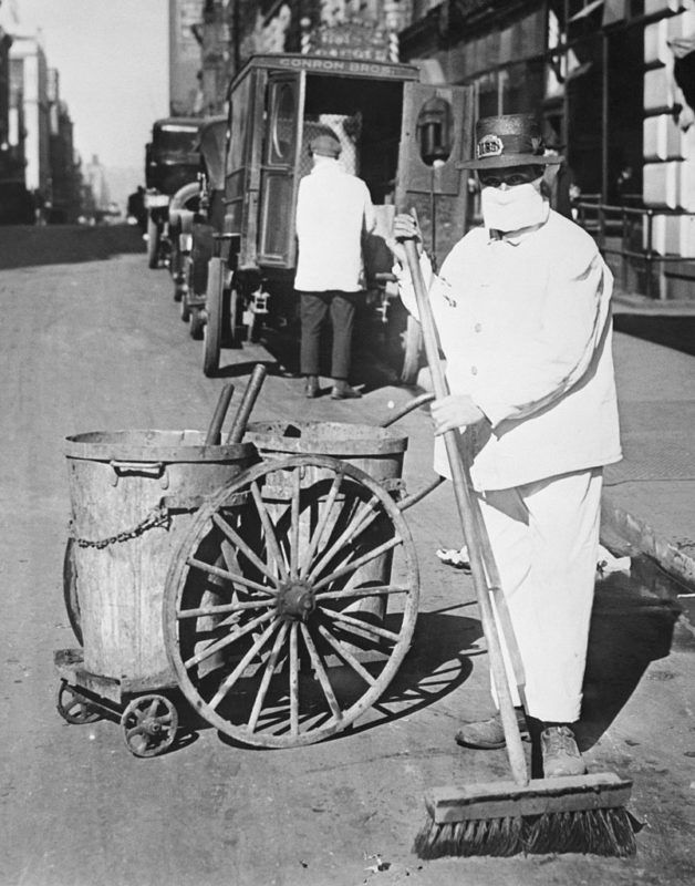 """(Original Caption) New York Street cleaner wearing mask to check the spread of the influenza epidemic. """"Better be ridiculous then dead"""" is the view of one official. BPA2# 3019"""
