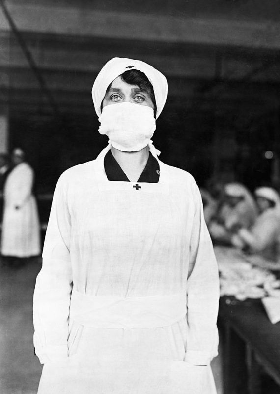 (Original Caption) Influenza epidemic of 1917. At a Red Cross work room, this young lady has just completed an influenza mask. Women in the background are making these masks. Photograph.