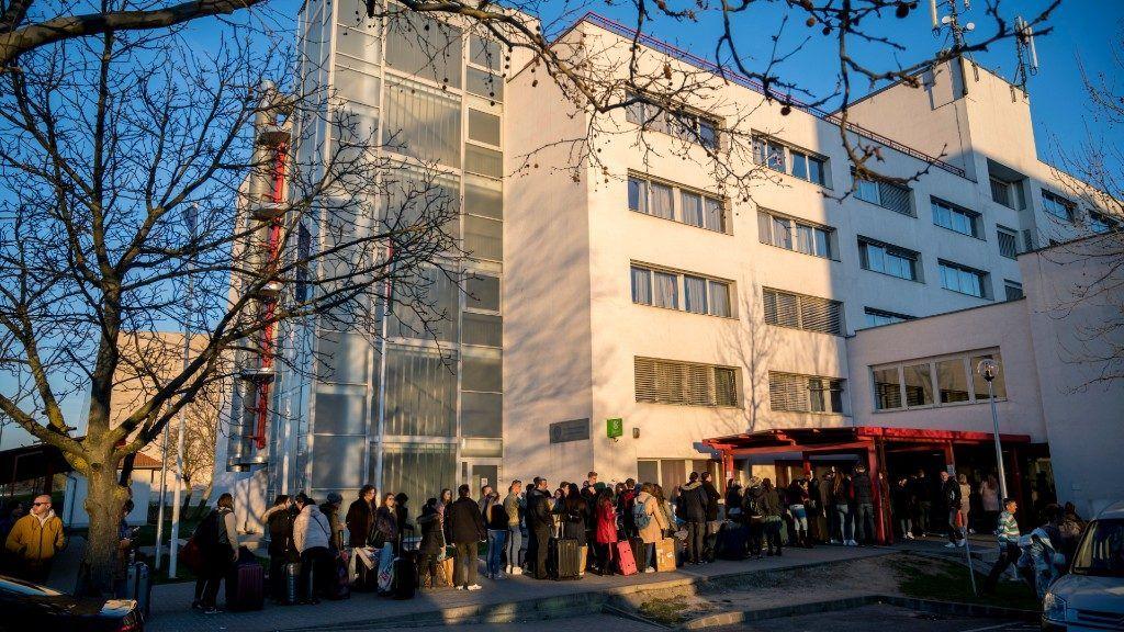 Hallgatók várakoznak a kiköltözésre a Pécsi Tudományegyetem Szalay László Kollégium épülete előtt (Fotó: MTI/Sóki Tamás)