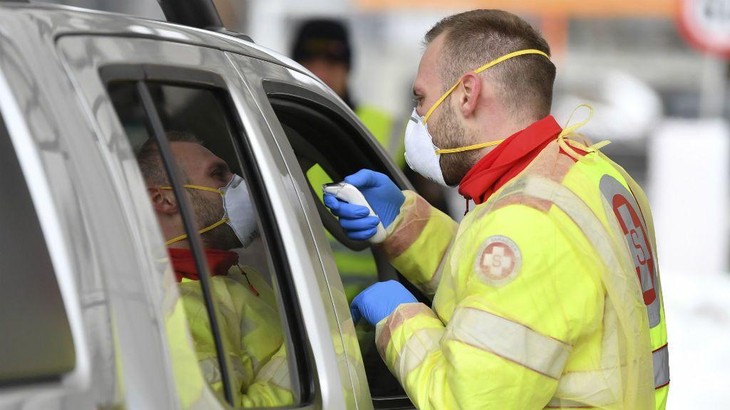 Egészségügyi dolgozó egy utas testhőmérsékletét méri az ausztriai Gries am Brenner település és az osztrák-olasz határ közötti parkolóban 2020. március 10-én. Az osztrák határon az Olaszországból érkező járműveket szúrópróbaszerűen ellenőrzik a koronavírus-járvány terjedése miatt.MTI/AP/Kerstin Joensson