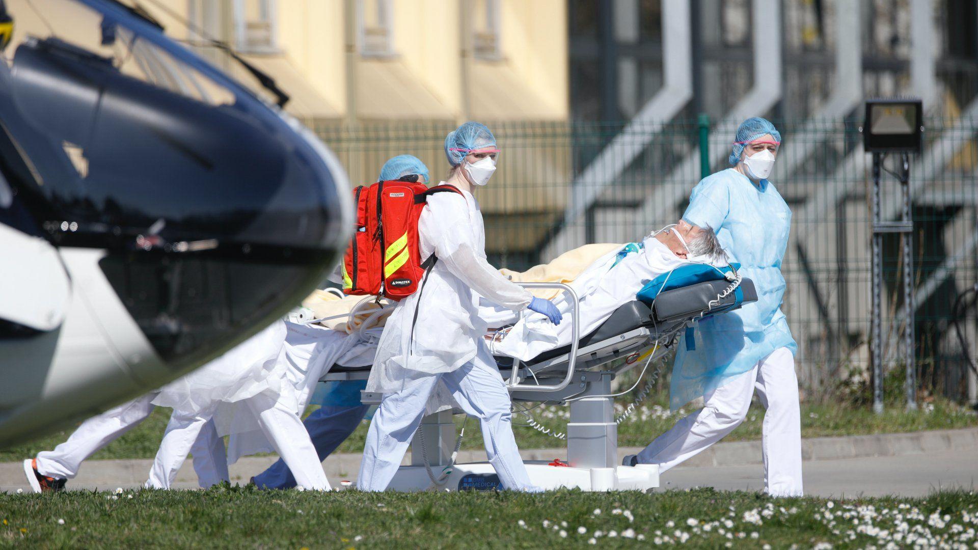 A koronavírussal fertőzött betegek egyikét szállítják el ápolók a kelet-franciaországi Mulhouse város kórházából 2020. március 23-án (Fotó: MTI/AP)