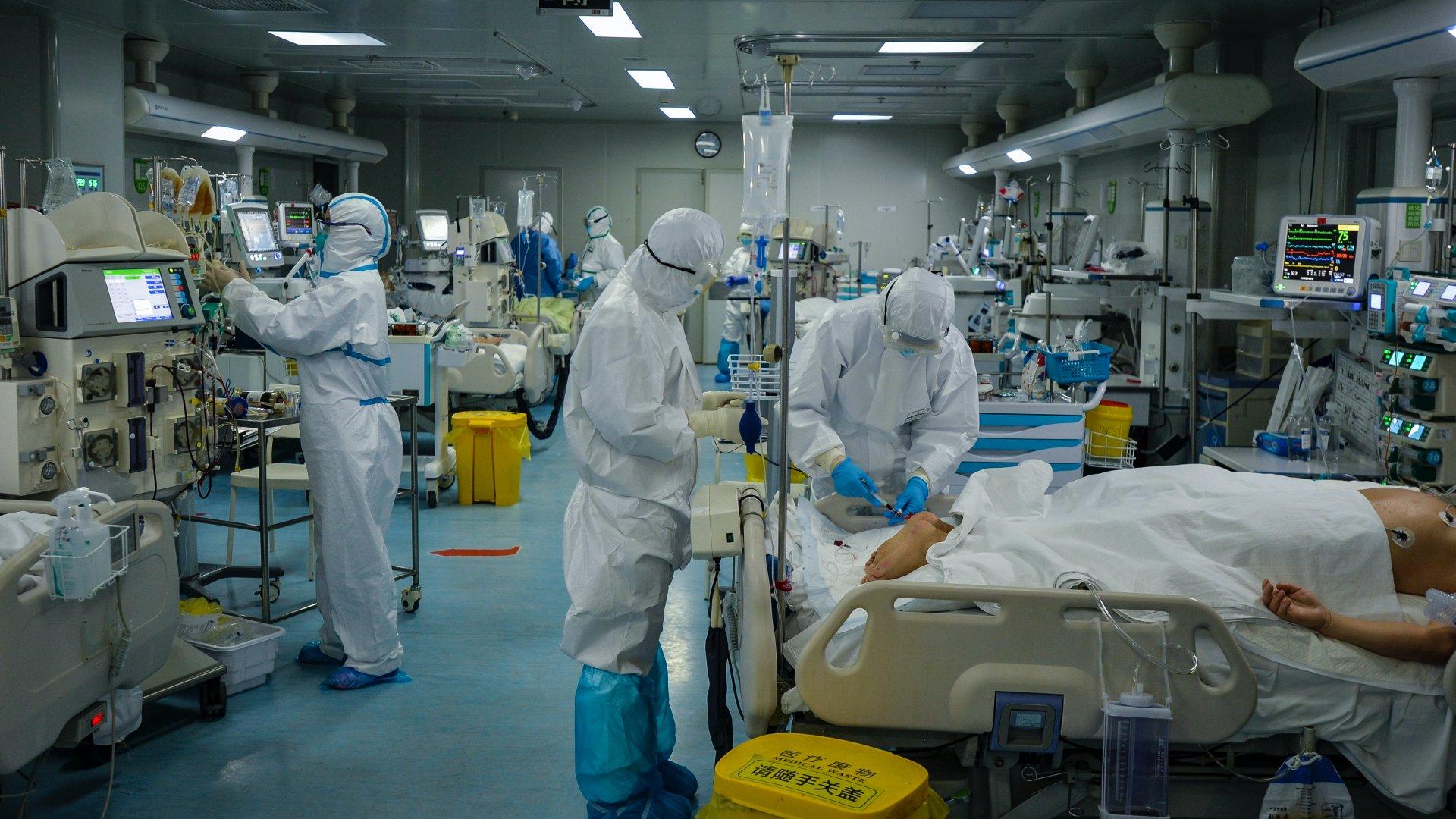 A járványügyi hatóság védőöltözetet viselő munkatársai egy kórház intenzív osztályát készítik elõ a tüdőgyulladást okozó új koronavírussal fertőzöttek fogadására a járvány gócpontjában, a kelet-kínai Hupej tartomány székhelyén, Vuhanban 2020. február 24-én (Fotó: MTI/EPA/Si Cse)