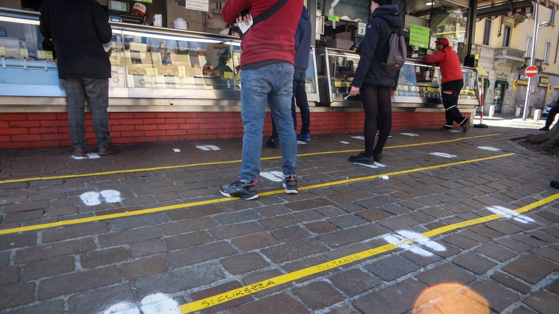 Járdára festett vonalak és lábnyomok jelzik a sorban álló emberek számára a koronavírus-fertőzés megelőzéséhez szükséges biztonságos távolságot egy milánói utcai étkezde előtt 2020. március 11-én (Fotó: MTI/EPA/ANSA/Matteo Corner)