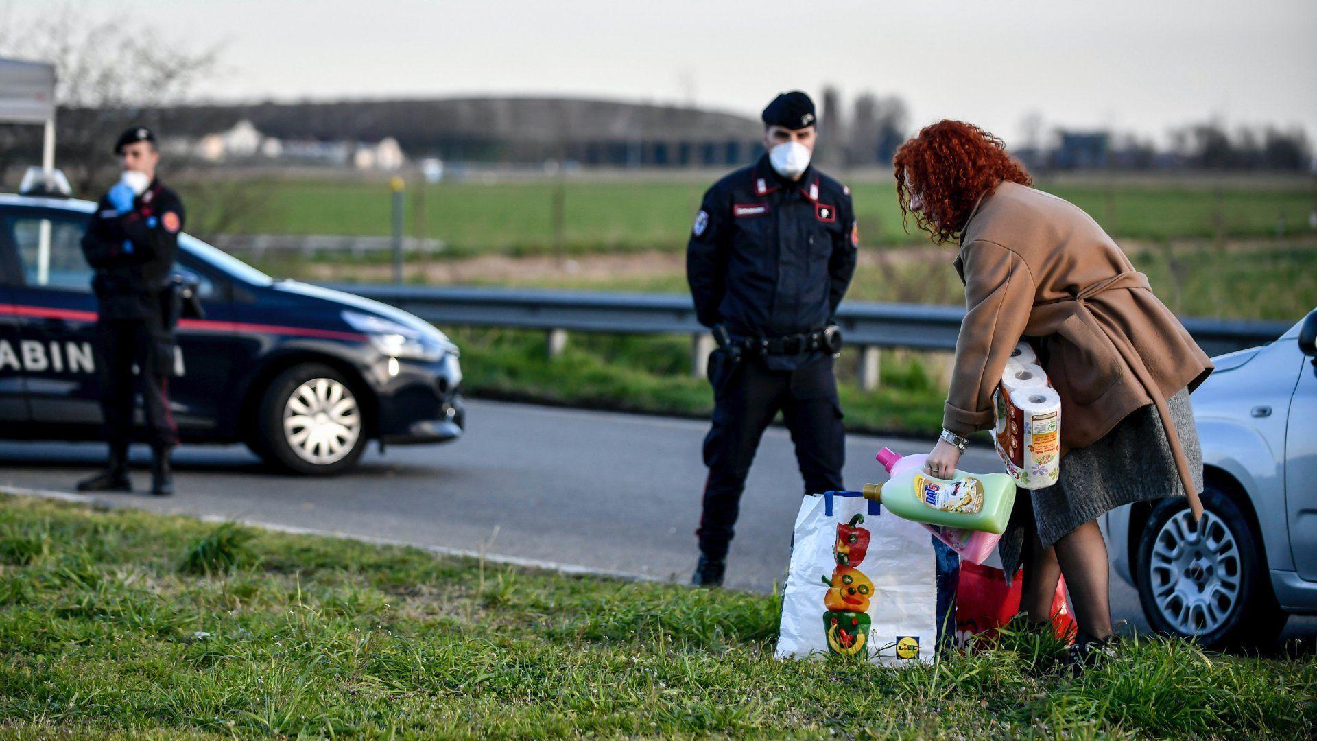 Rendőrségi útzár előtt vár egy nő, hogy bemehessen a lombardiai Casalpusterlengo városába 2020. március 8-án, miután a koronavírus-járvány további terjedésének megállítására az olasz kormány vesztegzár alá vonta az észak-olaszországi Lombardia tartományt és az országrész 15 másik városát (Fotó: MTI/AP/LaPresse/Claudio Furlan)