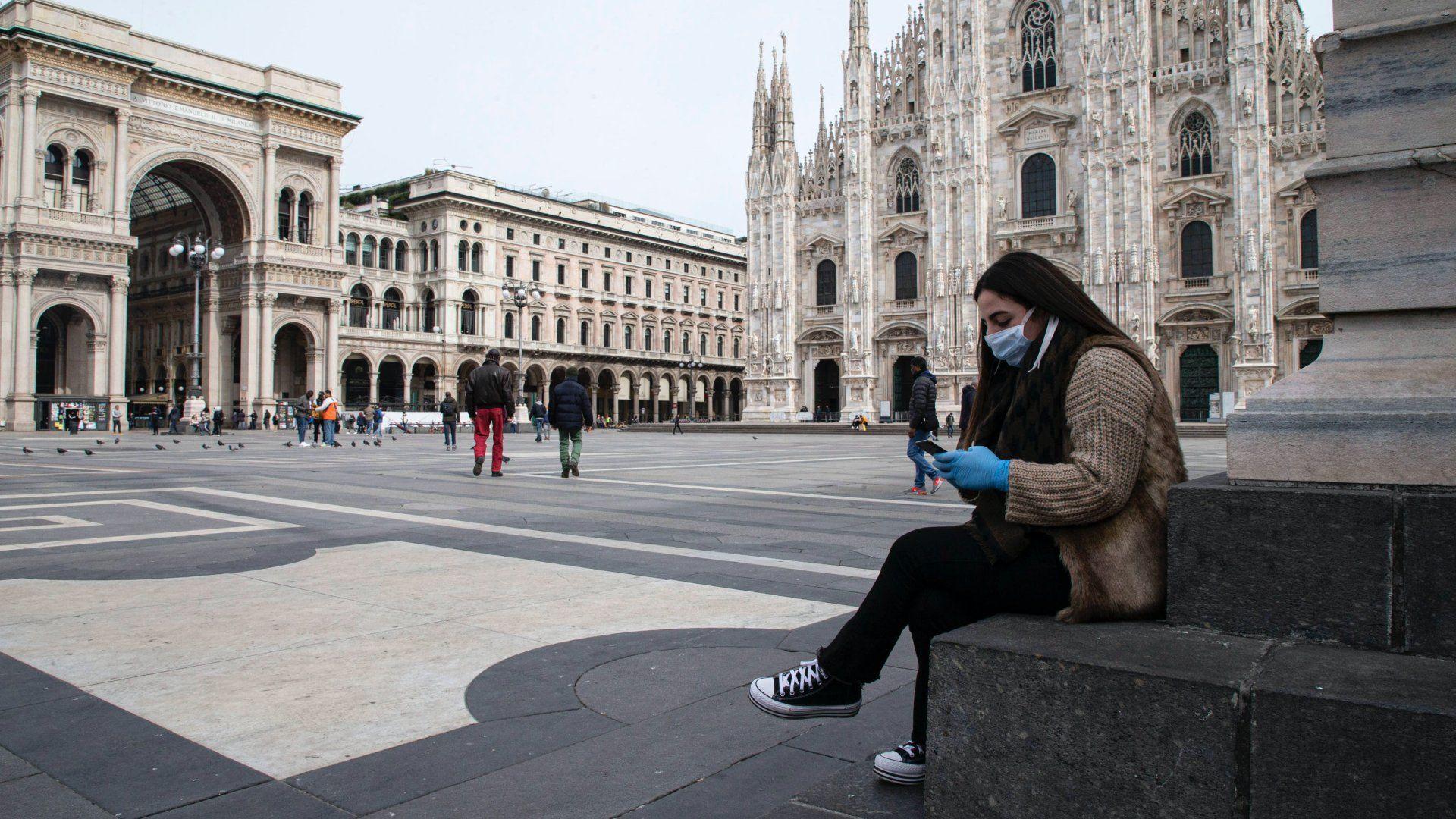 Védőmaszkos nő nézi a telefonját a milánói dóm előtt 2020. március 10-én (fotó:MTI/EPA/ANSA/Marco Ottico)
