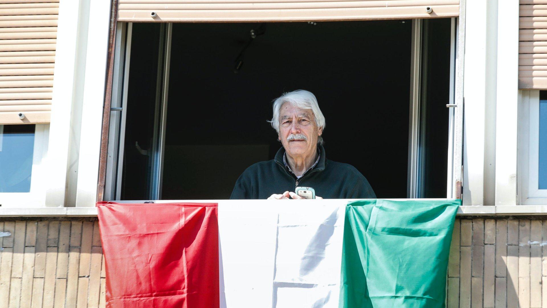 Nemzeti színű zászlót lógat ki idős férfi lakása ablakából Rómában a koronavírus-járvány miatt bevezetett kijárási tilalom idején, 2020. március 20-án (fotó: MTI/EPA-ANSA/Giuseppe Lami)