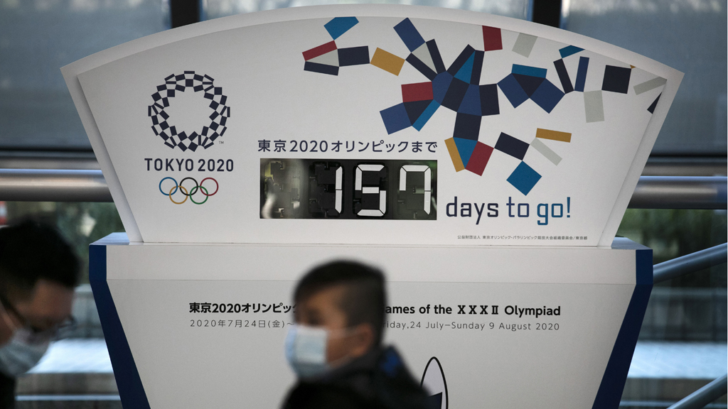 Maszkos fiú egy olimpiai tábla előtt