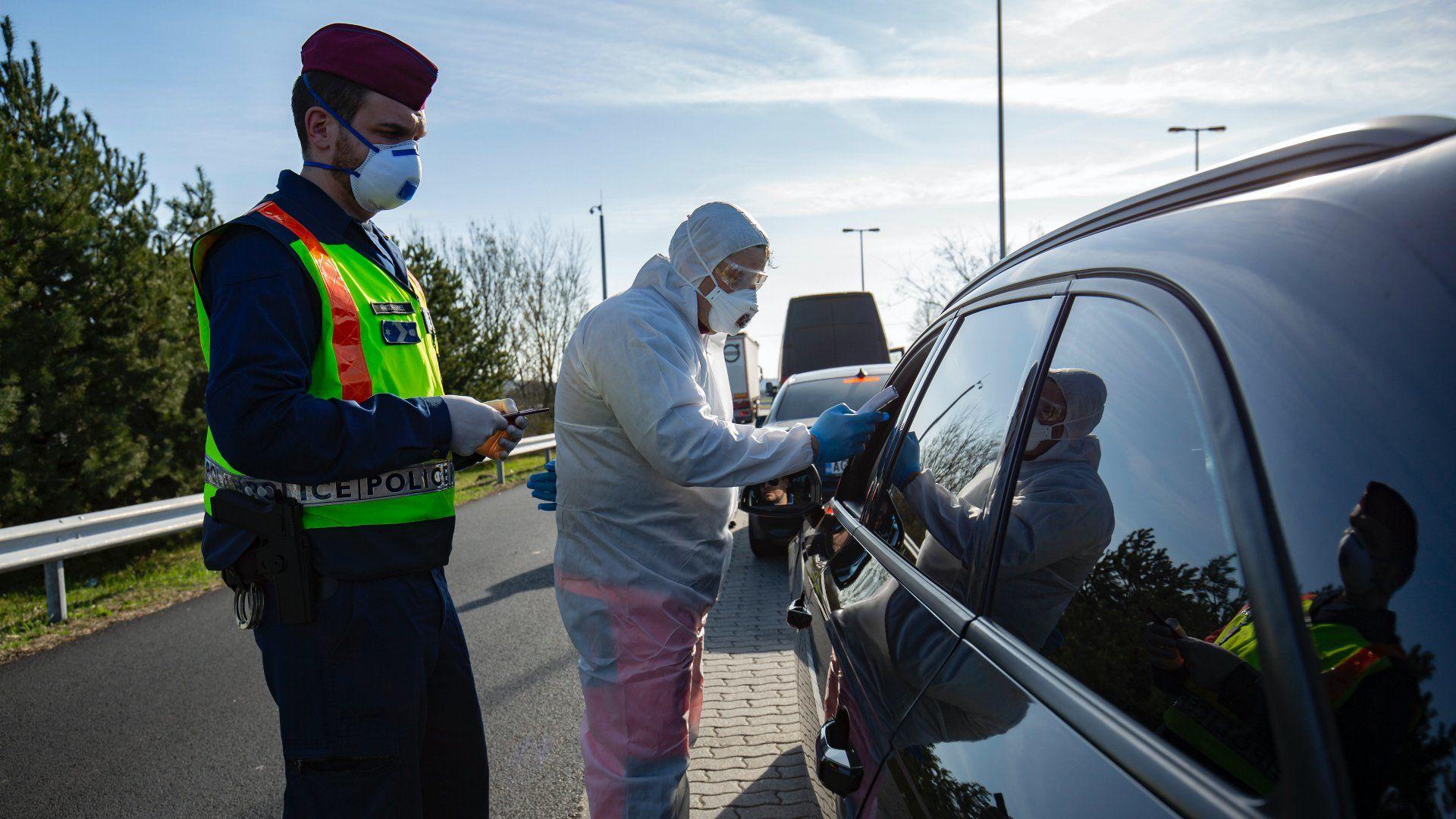 Az új koronavírus-járvány miatt bevezetett határellenőrzésen rendőr és mentő ellenőriz egy beérkező autóst a magyar–szlovén határ közelében, az M70-es autópálya csörnyeföldi pihenőhelyénél 2020. március 12-én (Fotó: MTI/Varga György)
