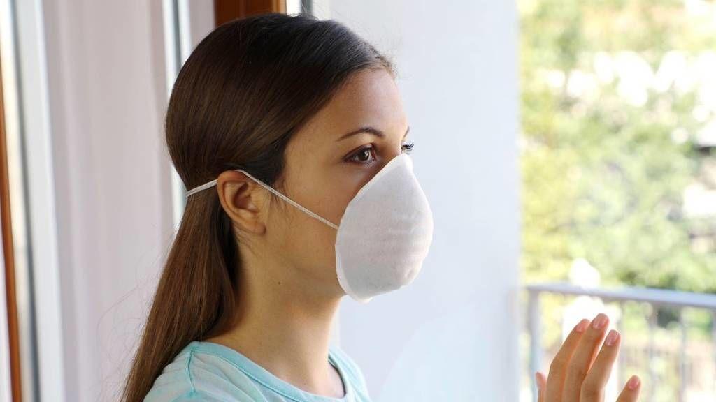 Nő karanténban, maszkban