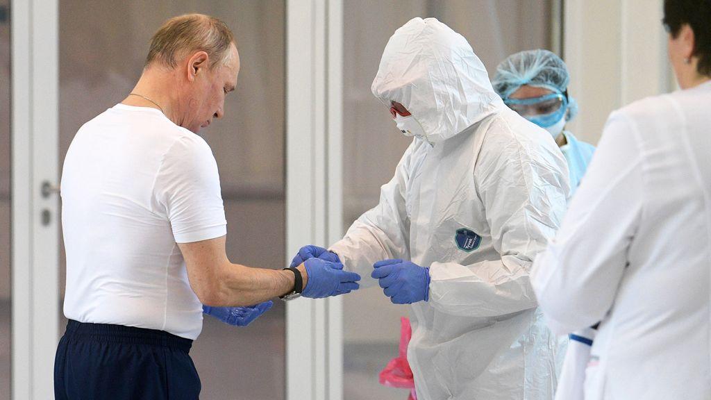 Vlagyimir Putyin orosz elnök (k) kesztyûjét segít levenni egy szakember, miután az államfõ meglátogatta azokat a pácienseket, akiket koronavírus-fertõzés gyanújával megfigyelés alatt tartanak egy moszkvai kórházban.(Fotó: MTI/EPA/Szputnyik pool/Alekszej Druzsinyin)