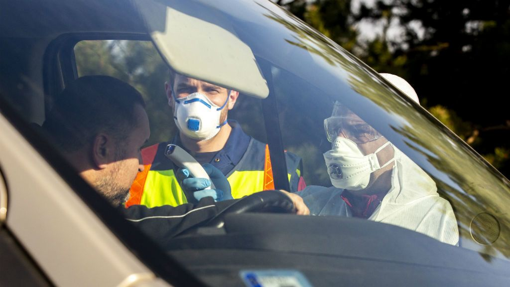 A tüdőgyulladást okozó új koronavírus-járvány miatt bevezetett határellenőrzésen rendőr és mentő ellenőriz egy beérkező autóst a magyar-szlovén határ közelében, az M70-es autópálya csörnyeföldi pihenőhelyénél 2020. március 12-én. A szlovén, valamint az osztrák schengeni határon ellenőrzést vezettek be.MTI/Varga György