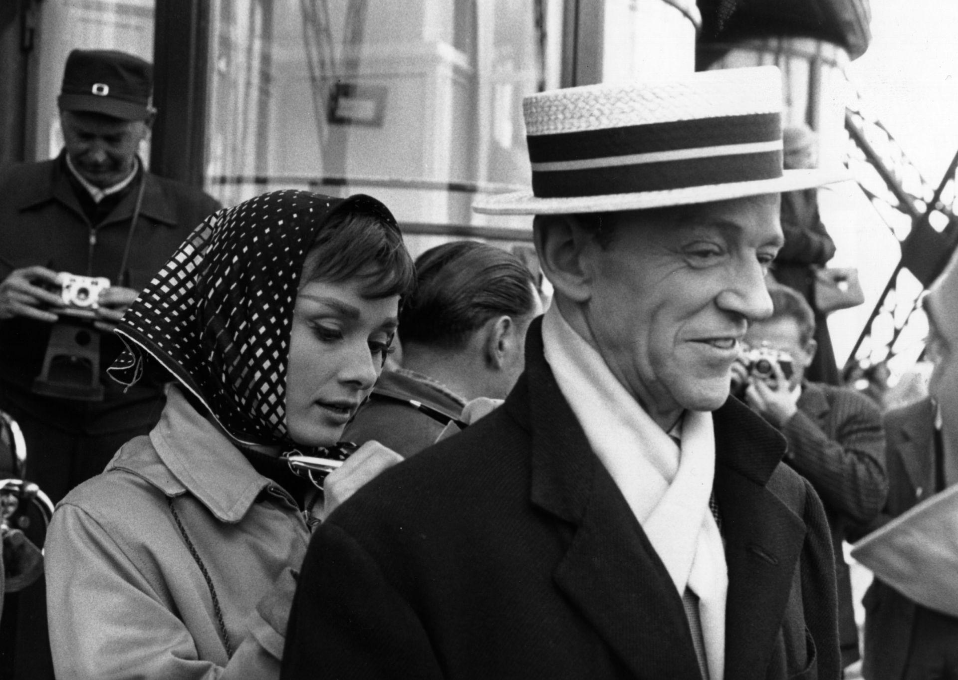 Audrey Hepburn épp filmbéli partnerének Fred Astaire-nek a hátát használja íródeszkának a Funny Face forgatásán, 1956-ban.