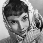 Audrey Hepburn fejkendős, kabátos fotója.