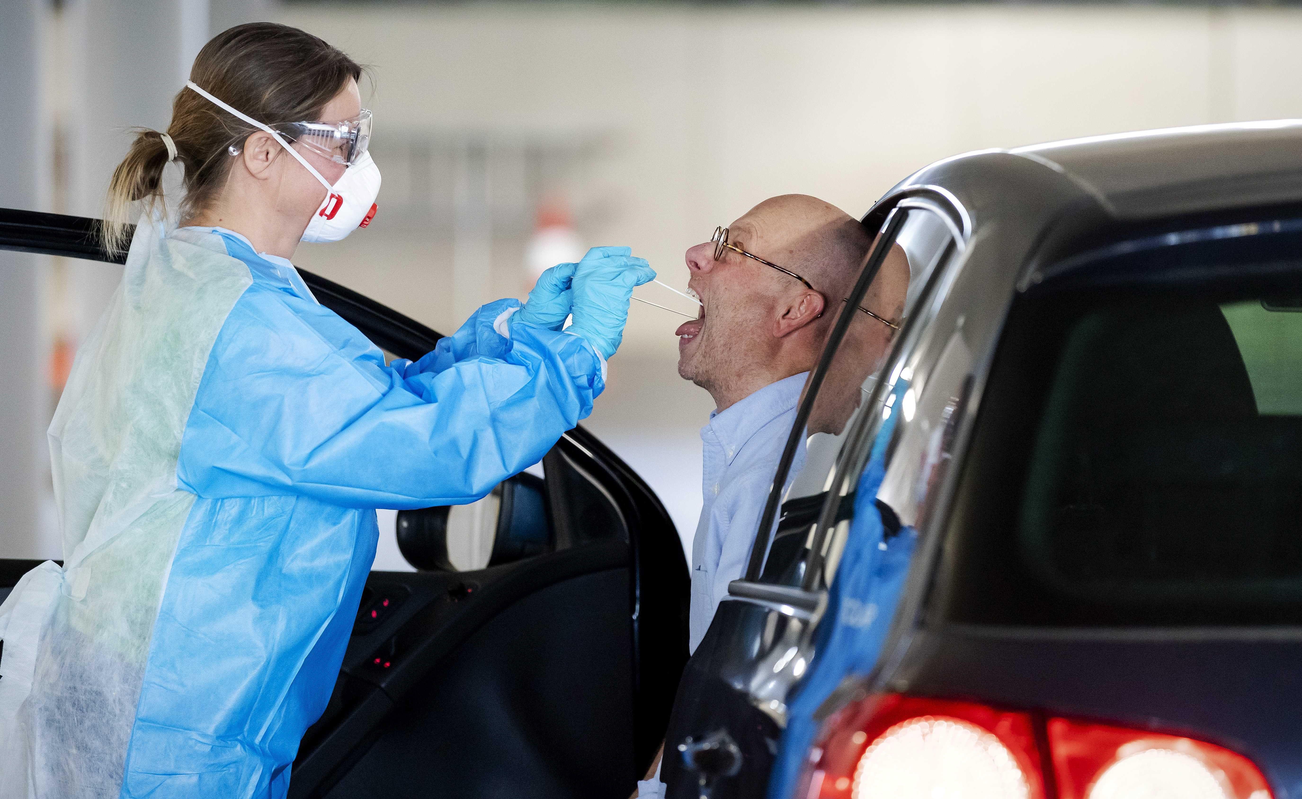 Autós torkából vesz vizsgálati mintát egy egészségügyi dolgozó egy rotterdami utcai tesztelőponton a koronavírus-járvány idején, 2020. április 6-án (Fotó: MTI/EPA/ANP/Robin Van Lonkhuijsen)