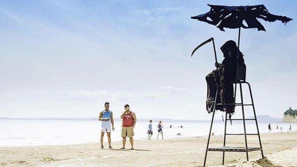 kaszásjelmezben ül egy férfi a strandon