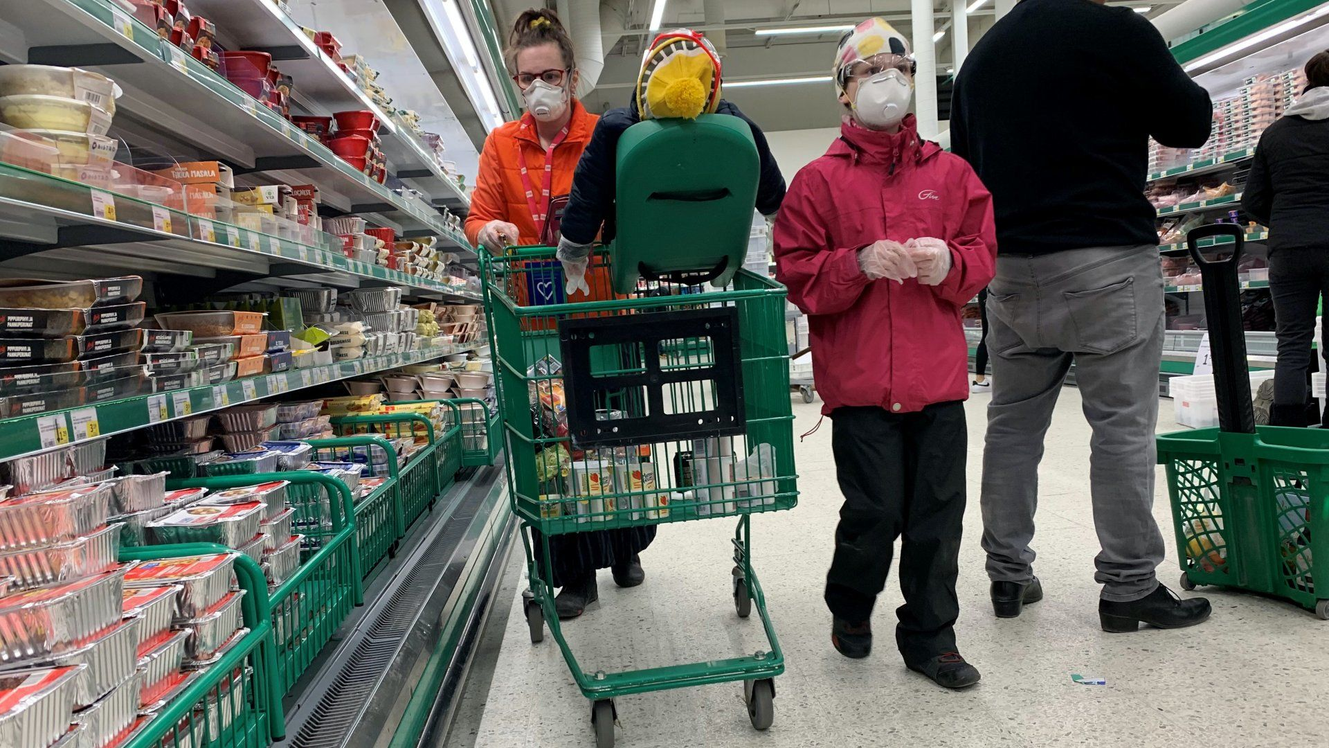Szájmaszkos vásárlók egy finnországi szupermarketben