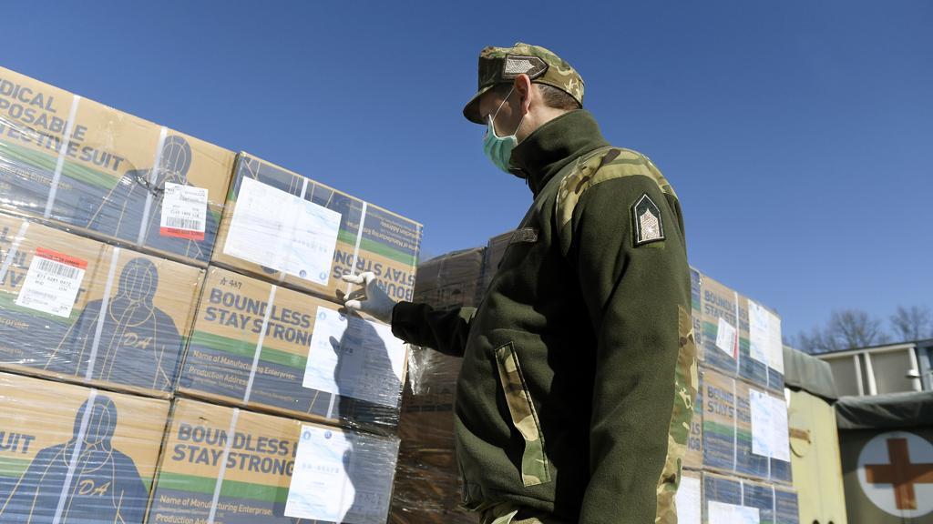 A Kínából repülõgépen érkezett huszonnyolc raklapnyi orvosi védõeszköz lepakolását ellenõrzi egy katona a Magyar Honvédség Egészségügyi Központjának udvarán. (Fotó:MTI/Koszticsák Szilárd)