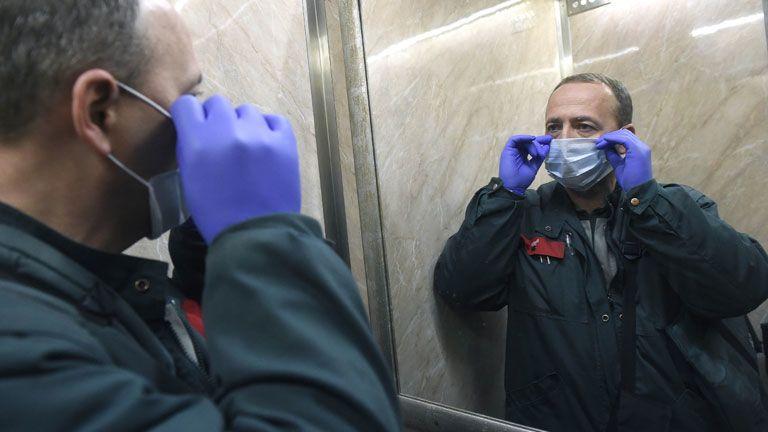 Kézbesítésre igyekvő postás védőfelszerelésben - MTI/Bruzák Noémi