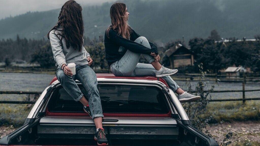 Két lány egy autó tetején.