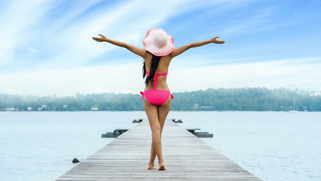Egy lány áll borús ég alatt bikiniben egy stégen