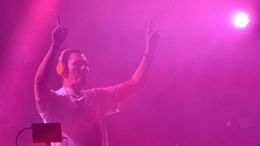 Tiesto a DJ pult mögött felemelt kézzel