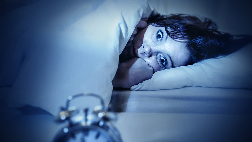 young woman in bed with alarm clock and eyes opened suffering insomnia and sleep disorder thinking about his problem on dark studio lighting in sleeping and nightmare issues
