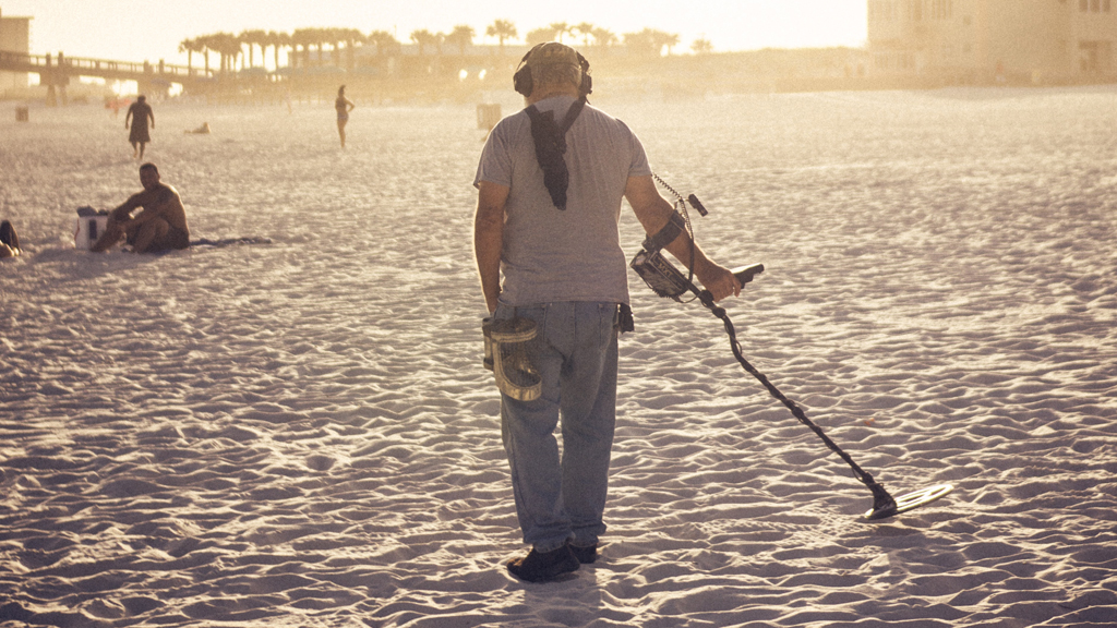 férfi fémdetektorral matat a homokban