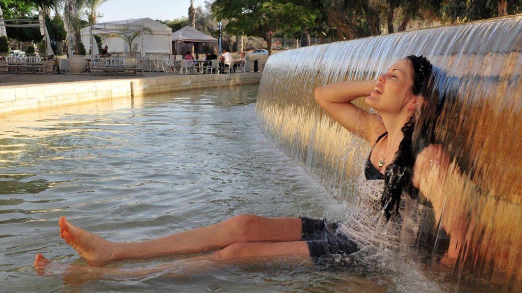 Lány hűsöl egy szökőkűtban a nyári hőségben